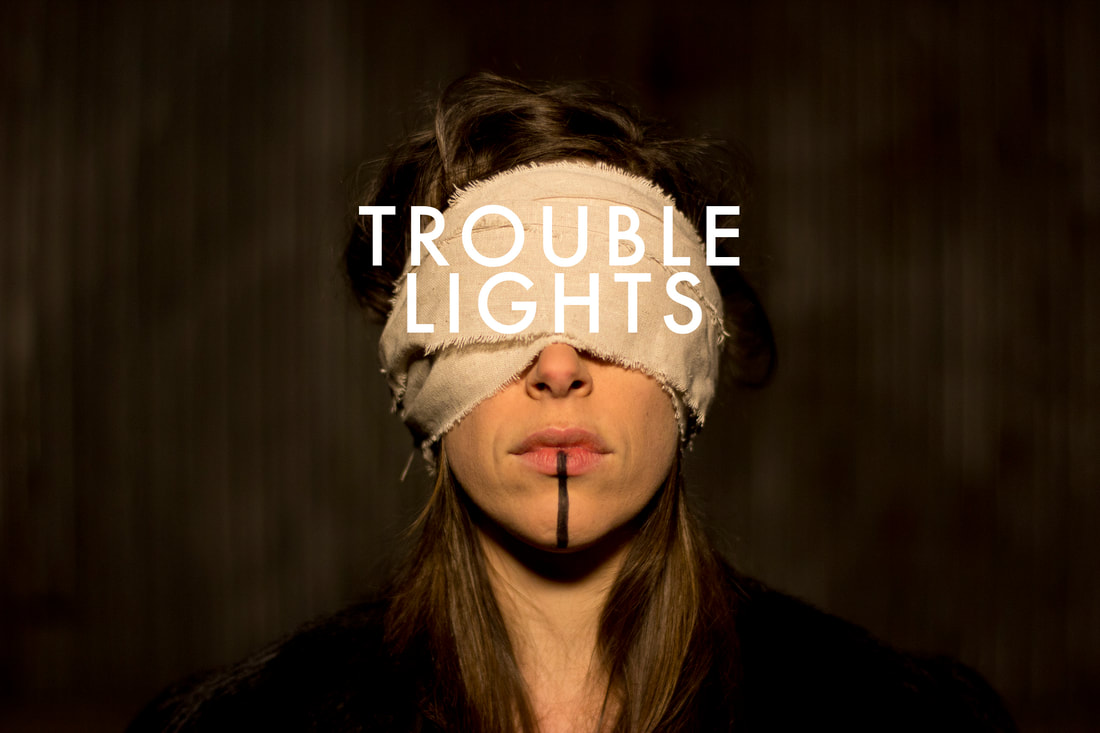 Adrien Logsdon of Trouble Lights blindfolded with text Trouble Lights over the blindfold.